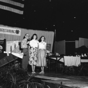 Two girls standing onstage next to a man speaking into a microphone, during North Carolina State 4-H Club Week