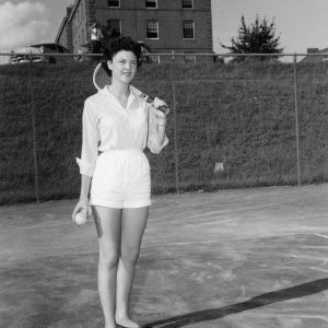 4-H club member Lois Immons playing tennis while attending North Carolina State 4-H Club Week