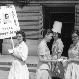 "Young women campaigning for Mary Ann Boles, with sign reading ""Vote for Mary Ann Boles, State President,"" during North Carolina State 4-H Club Week"