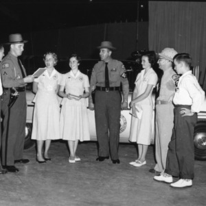 4-H club members standing with two highway patrolmen as they give a demonstration at North Carolina State 4-H Club Week