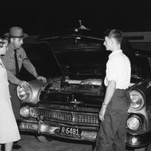 Two 4-H club members standing with a highway patrolman watching a demonstration at North Carolina State 4-H Club Week