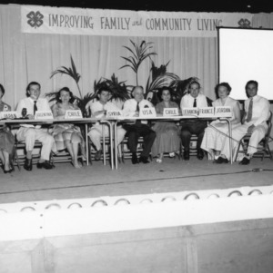 Group of panelists onstage during North Carolina State 4-H Club Week event, L. R. Harrill, center