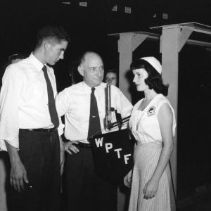 L. R. Harrill, center, and 4-H club members in front of WPTF radio microphone, during North Carolina State 4-H Club Week