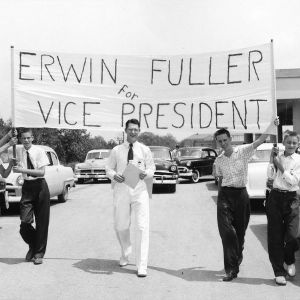 """Group of boys marching in parking lot with sign reading """"Erwin Fuller for Vice President,"""" during North Carolina State 4-H Club Week"""