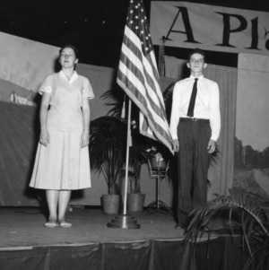 Young woman and young man standing on stage with American flag between them, during North Carolina State 4-H Club Week