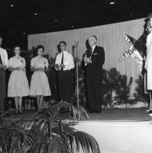 L. R. Harrill and 4-H club members standing on stage during North Carolina State 4-H Club Week