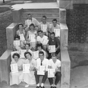 "4-H club members sitting on steps and holding up copies of ""Clover leaves"" newsletter during North Carolina State 4-H Club Week"