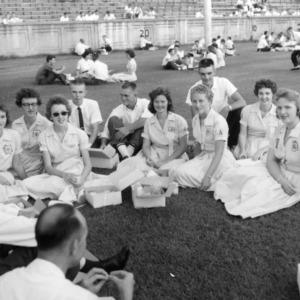 4-H club members picnicking on football field during North Carolina State 4-H Club Week