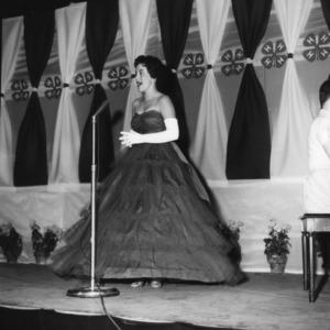 Woman onstage speaking into microphone during North Carolina State 4-H Club Week