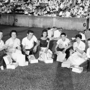 4-H club members eating box lunches on football field during North Carolina State 4-H Club Week