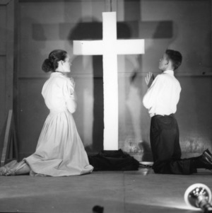 4-H club boy and girl onstage, praying to a cross, during North Carolina State 4-H Club Week