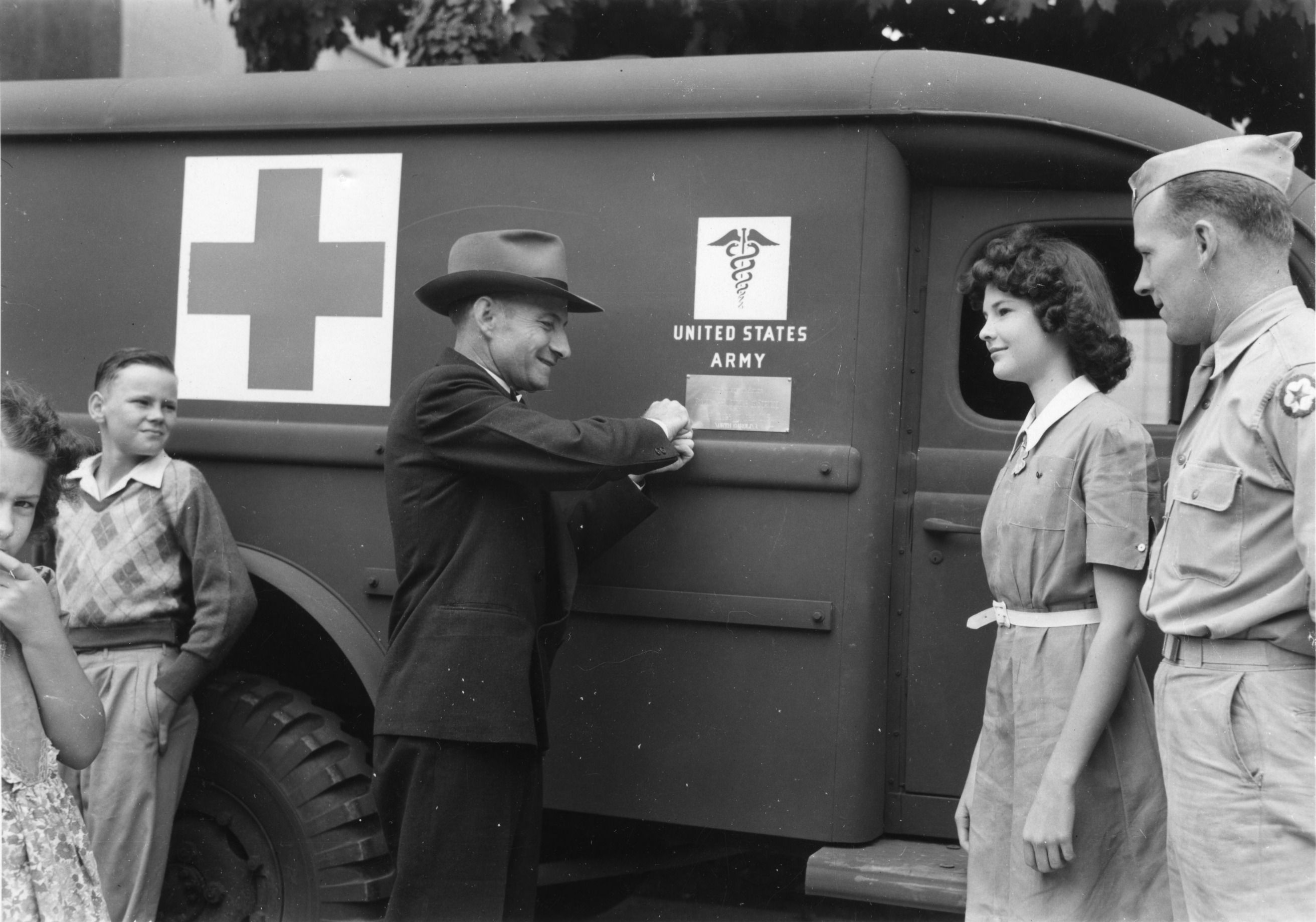 L. R. Harrill revealing the plaque placed on an ambulance donated to the United States Army Medical Department in honor of former 4-H club members now serving in the armed forces