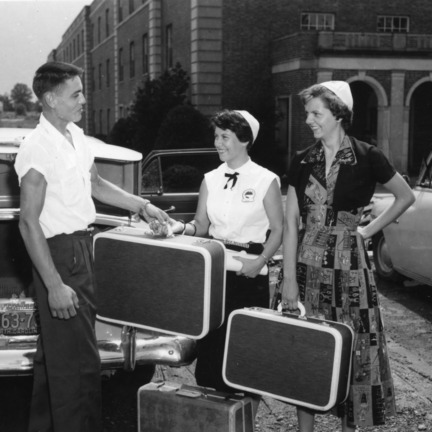 Young man helping two young women with their suitcases