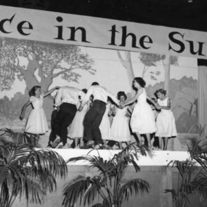 """4-H club members acting onstage under a banner reading """"Place in the Sun,"""" during North Carolina State 4-H Club Week"""