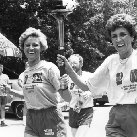 Nora Lynn Finch (left) and Kay Yow carrying United States Olympic Festival Torch through North Carolina State University campus, fall 1987
