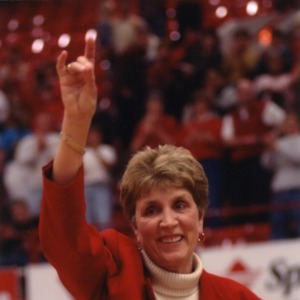 Kay Yow making wolf symbol with her hands at women's basketball game