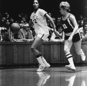 N.C. State's #12 Trudi Lacey dribbles down the court with UCLA opponent on defense