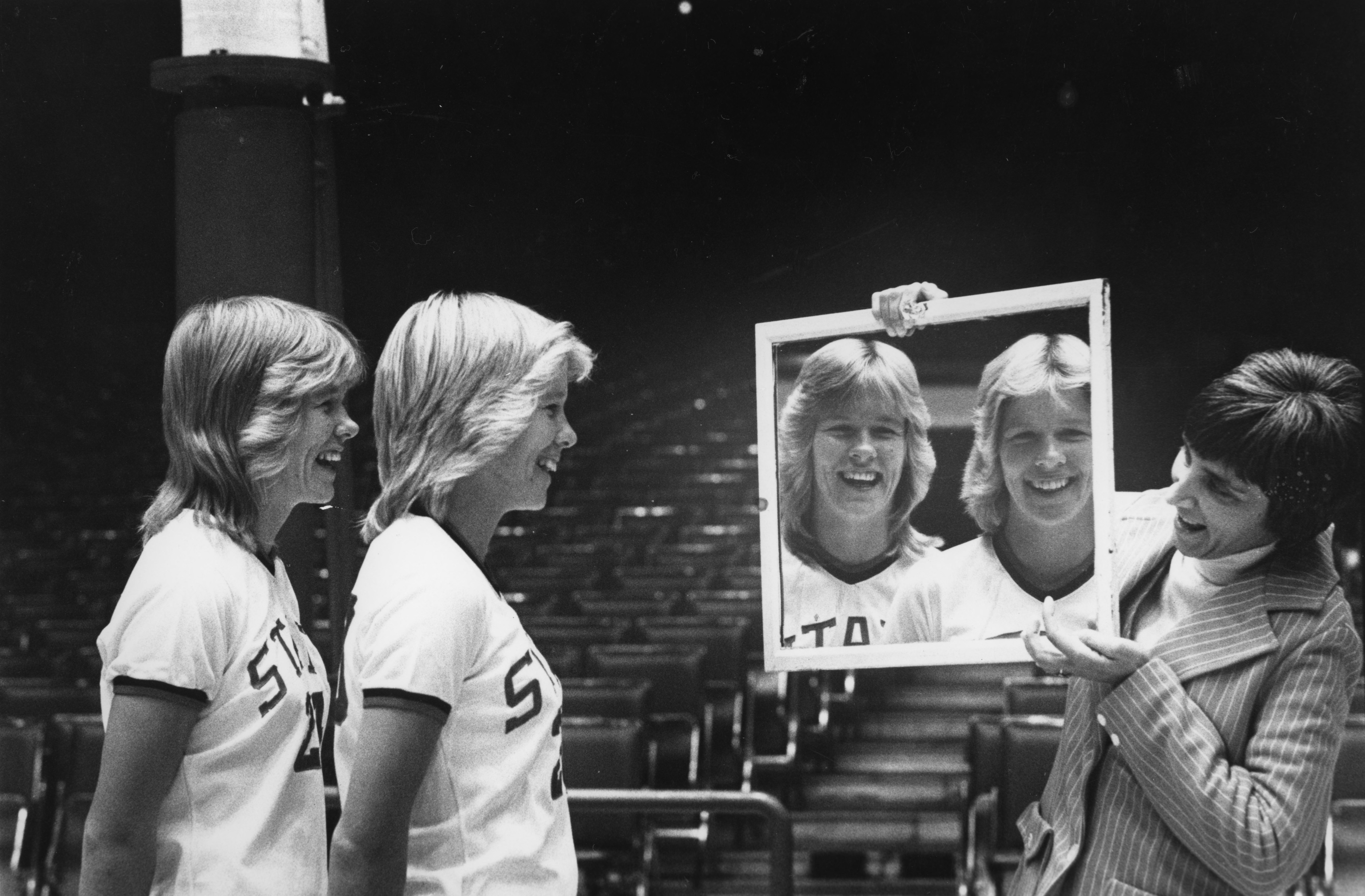 Faye and Kaye Young look at their reflections in mirror held by Head Coach Kay Yow
