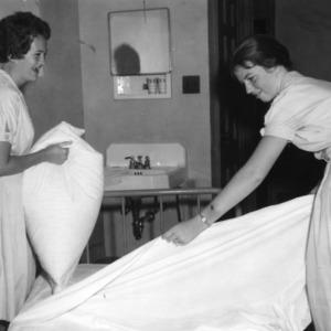 Two 4-H girls make bed during North Carolina State 4-H Club Week