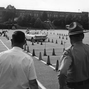 North Carolina State Highway patrolman and an unidentified man watching a driver practice skilled driving at North Carolina State 4-H Club Week held at North Carolina State University in Raleigh, July 1965