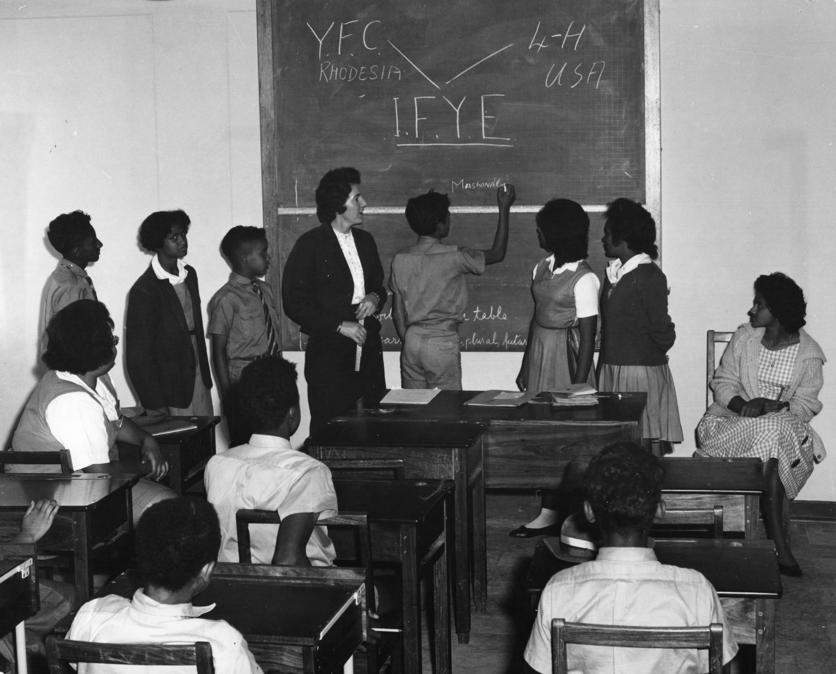 Youth participating in the International Farm Youth Exchange (IFYE) program, writing their names on a blackboard