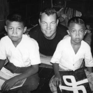 Bobby Smith from Perquimans County, North Carolina, participating in the Internation Farm Youth Exchange program, sitting with two children in Burma, March 1960