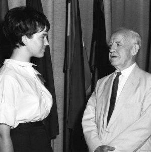 4-H club girl speaking with an unidentified man with the United Nations flag in the background as part of the 4-H citizenship program