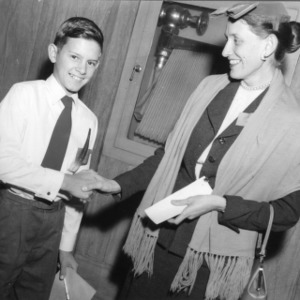 4-H club member shaking hands with an unidentified woman
