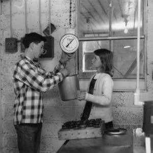 4-H club members weighing a bucket