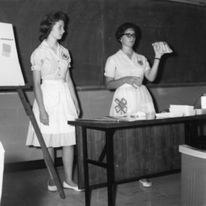 Eileen Dishman and Jane Kelly, of Mooresville (Iredell County), North Carolina, 1963 state winners in 4-H club poultry marketing team demonstration