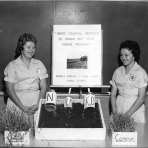 """Brenda Creech and Joan Harris of Vance County with an exhibit on """"Using Coastal Bermuda to Round Out Your Forage Program,"""" during North Carolina State 4-H demonstration competition"""
