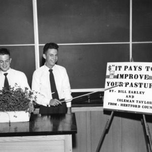 """Bill Earley and Coleman Taylor, of Hertford County, North Carolina, with exhibit entitled """"It Pays to Improve Your Pasture,"""" during North Carolina State 4-H demonstration competition, 1955"""