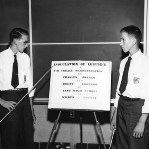 """Charles Jordan and Brent Edwards, of Wilkes County with winning exhibit entitled """"Inoculation of Legumes,"""" during North Carolina State 4-H demonstration competition, 1955"""