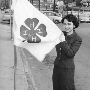 4-H club member displaying the 4-H flag