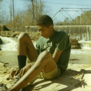 4-H club member removing his shoes, preparing to clear garbage from a river, 1970
