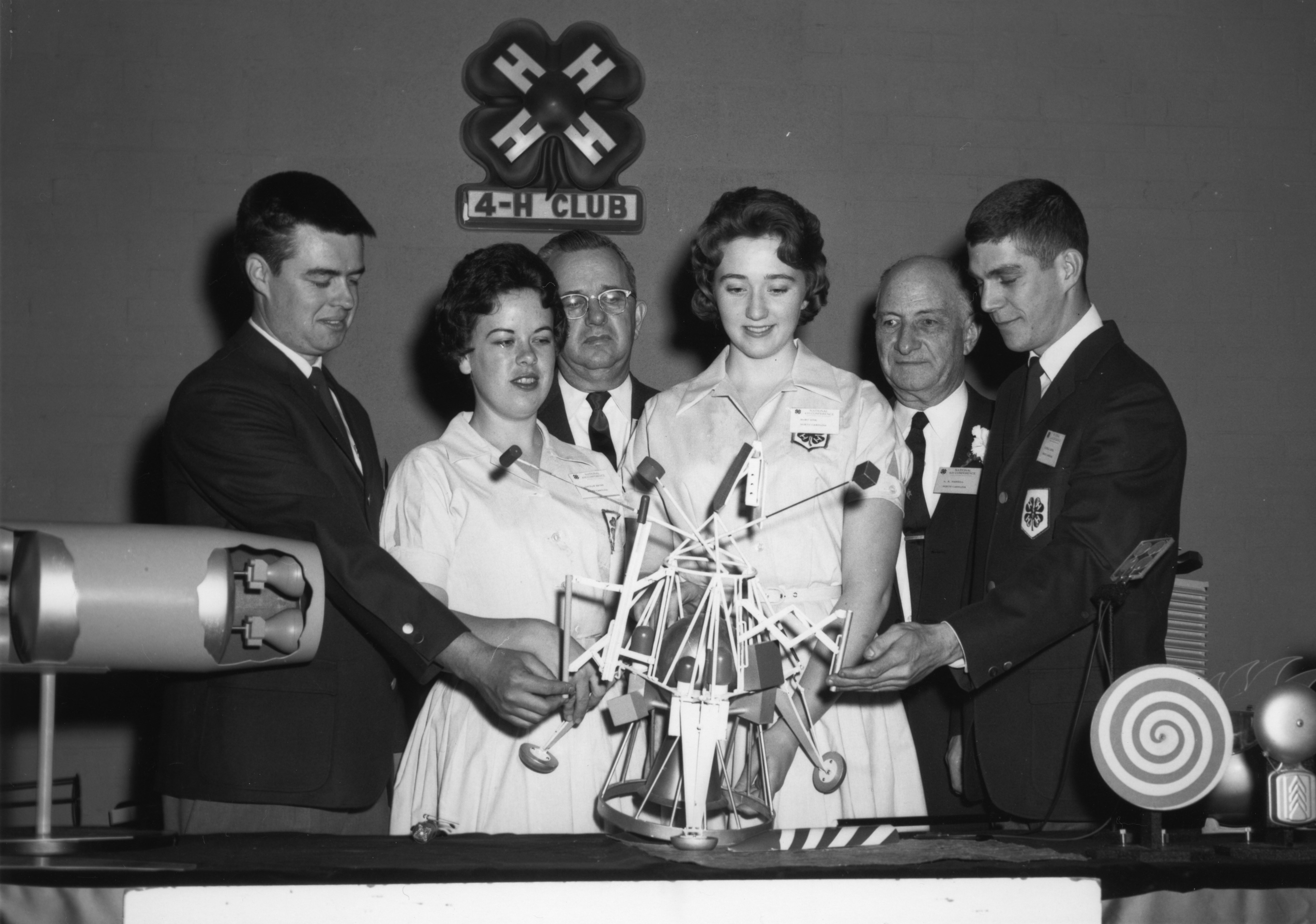 4-H club members examining model of a satellite. L. R. Harrill, second from right