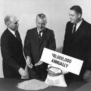 "NCSU Chancellor John Caldwell with unknown persons, possibly promoting ""1.6 in '66"" agricultural program."