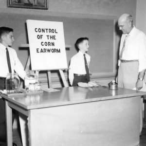 "4-H club boys with an exhibit on ""Control of the Corn Earworm,"" during North Carolina State 4-H demonstration competition"