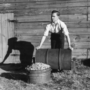 Rudolph Carl Ellis standing with his peanut crop and peanut roaster as a part of a 4-H club peanut project in Cumberland County, North Carolina