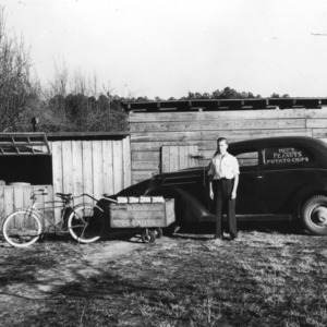 An unidentified man standing in front of a peanut delivery vehicle