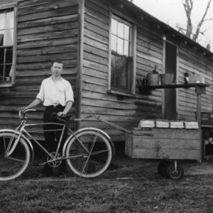 Rudolph Ellis standing with his bicycle and cart as a part of a 4-H club peanut project in Cumberland County