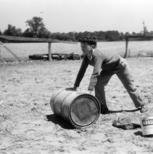 An unidentified boy rolls a peanut roasting barrel as part of a 4-H club peanut project in Chowan County, North Carolina