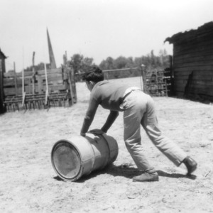 An unidentified boy rolls a peanut roasting barrell as part of a 4-H club peanut project in Chowan County, North Carolina