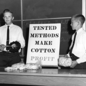 "4-H club boys with an exhibit, ""Tested methods Make Cotton Profit,"" during North Carolina State 4-H demonstration competition"