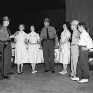 4-H club members participating in the safety demonstration with two highway patrol officers at North Carolina State 4-H Club Week held at North Carolina State College in Raleigh