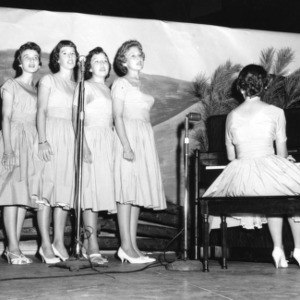 Four 4-H club girls singing while a fifth plays the piano in a North Carolina State 4-H Club Week performance at North Carolina State College in Raleigh