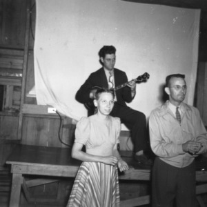 George [Forthing?] playing guitar while Miss Garney and Robb [Shoffour?] clap in a North Carolina State 4-H Club Week performance at North Carolina State College in Raleigh