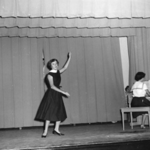 4-H club girl dancing on stage while another plays piano at a North Carolina State 4-H Club Week performance