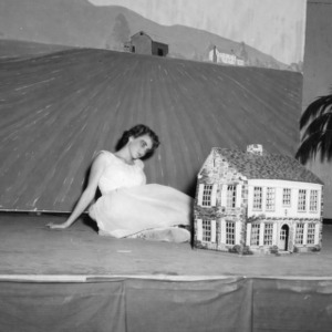 4-H club girl looking into a dollhouse in a performance at North Carolina State 4-H Club Week at North Carolina State College in Raleigh