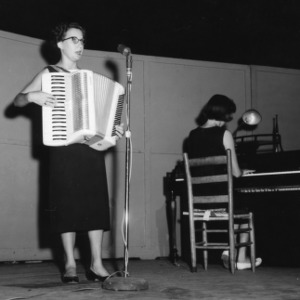 4-H club girl playing the accordion while singing and accompanied by another 4-H club girl playing piano in a performance at North Carolina State 4-H Club Week at North Carolina State College in Raleigh